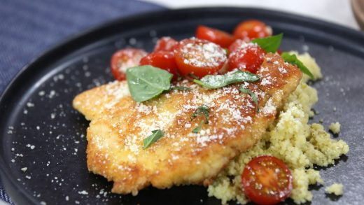 Parmesan chicken with quick sautéed tomatoes on pesto couscous
